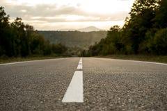 Strada della montagna che retrocede nella distanza, il tramonto, l'orizzonte della prospettiva del supporto fotografie stock libere da diritti