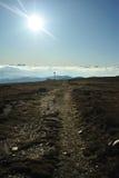 Strada della montagna con il sole nel palo della marcatura e della parte anteriore Fotografia Stock