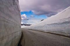 Strada della montagna con l'alta parete della neve Immagini Stock