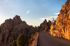Strada della montagna con le rocce al tramonto Strada della montagna con la scogliera di luce solare Fotografia Stock