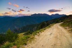 Strada della montagna della sporcizia che conduce al passaggio di alta montagna in Italia Vista di Expasive al tramonto, cielo dr Immagini Stock