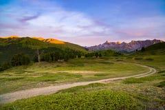 Strada della montagna della sporcizia che conduce al passaggio di alta montagna in Italia Vista di Expasive al tramonto, cielo dr Fotografia Stock