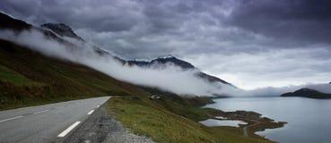 Strada della montagna lungo un lago della montagna nelle alpi francesi Immagini Stock