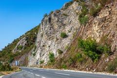 Strada della montagna in Macedonia Alta roccia protetta da rete d'acciaio Paesaggio con le colline coperte di foresta Fotografie Stock Libere da Diritti