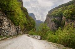 Strada della montagna nella gola fra le montagne di Caucaso fotografie stock libere da diritti