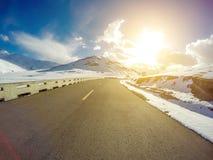 Strada della montagna della neve in Qinghai al tramonto, Cina fotografie stock