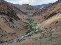 Strada della montagna, serpentina estrema sui pendii della valle dell'alta montagna in Himalaya: la strada discenderà dallo slo r Fotografia Stock