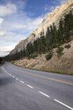 Strada della montagna sotto le scogliere rocciose maestose Fotografia Stock
