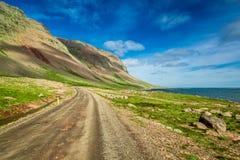 Strada della montagna vicino al mare artico, Islanda Immagini Stock