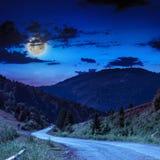 Strada della montagna vicino alla foresta di conifere con il cielo nuvoloso della luna Fotografia Stock