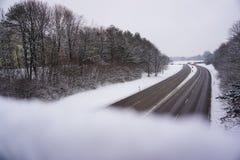 Strada della neve di inverno nella città con molti alberi Immagini Stock Libere da Diritti
