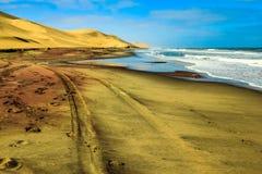 Strada della sabbia fra l'oceano e le dune del deserto Fotografia Stock Libera da Diritti