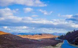 Strada della singola pista che conduce alle montagne Immagini Stock