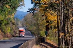 Strada di autunno con bello paesaggio ed il camion rosso dei semi Immagine Stock