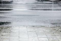 Strada di città bagnata dell'asfalto dopo pioggia fotografia stock