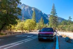 Strada di parco nazionale di Yosemite con l'automobile su una priorità alta Immagini Stock