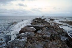 Strada di pietra che scompare nel mare ghiacciato di distanza Fotografia Stock