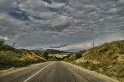 Strada di riciclaggio della montagna Strada della montagna nebbiosa in alte montagne Cielo nuvoloso con la strada della montagna  Fotografie Stock