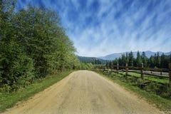 Strada di viaggio sul campo con erba verde e cielo blu con le nuvole sull'azienda agricola nel giorno soleggiato di bella estate  immagini stock