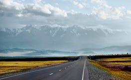 Strada diritta che passa attraverso la valle alle montagne Immagine Stock