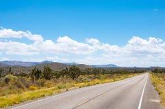 Strada diritta lunga attraverso un deserto di California Fotografia Stock