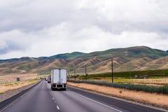 Strada a doppia carreggiata andante del caravan dei camion dei semi con il supporto serico dell'Idaho Immagine Stock Libera da Diritti