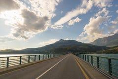 Strada a due corsie pavimentata sul lago dell'incrocio del ponte in paesaggio scenico e cielo lunatico Vista panoramica dalla mac Fotografie Stock Libere da Diritti