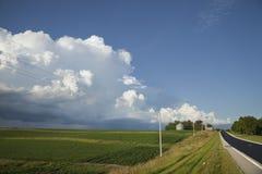 Strada e campi rurali di midwest sotto le grandi nuvole Immagini Stock Libere da Diritti