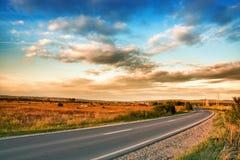 Strada e cielo blu rurali con le nubi fotografia stock libera da diritti