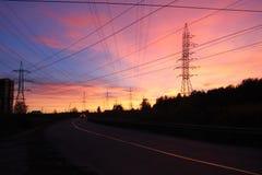 Strada e linee elettriche sui precedenti del cielo di tramonto Immagine Stock