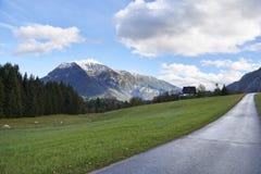 Strada e montagne un giorno soleggiato Abbellisca con un campo verde e le alpi austriache L'Austria, Gschwandt fotografie stock