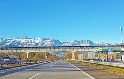 Strada e ponte in montagne svizzere innevate nell'inverno Fotografia Stock