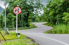 Strada e segnale di pericolo curvi serpente Fotografia Stock