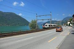 Strada e treno lungo il lago svizzero. Immagine Stock