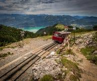 Strada ferrata di ferrovia a cremagliera alpina a Schafberg, in cui il treno a vapore prende i turisti su un picco di montagna ne fotografia stock