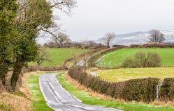 Strada ghiacciata con le colline e le siepi di arbusti leggermente innevate Immagini Stock