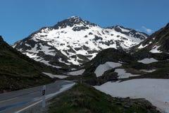 Strada girata pericolosa alta nelle alpi fra neve di fusione Fotografie Stock