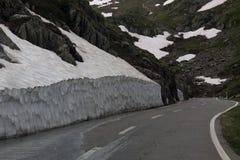 Strada girata pericolosa alta nelle alpi fra neve di fusione Immagini Stock