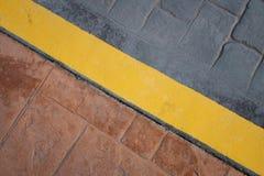 Strada, linea gialla del confine del marciapiede sul pavimento - fondo astratto immagini stock