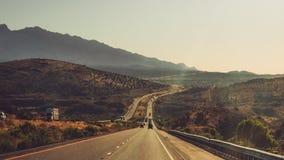 Strada lunga della finestra di viaggio stradale americano con le montagne fotografia stock