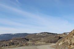 Strada lungo la montagna con le case sul pendio di collina Fotografia Stock