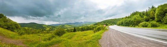 Strada in montagne con il cielo drammatico ed il panorama pesante delle nuvole fotografia stock