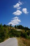Strada in montagne con le nuvole Immagini Stock
