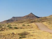 Strada namibiana della ghiaia con le montagne nella priorità bassa Immagine Stock Libera da Diritti