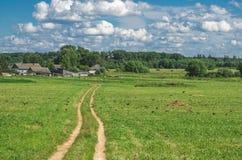 Strada nel campo sulla discesa della collina nel villaggio di distanza di estate e del cielo della nuvola Fotografia Stock Libera da Diritti