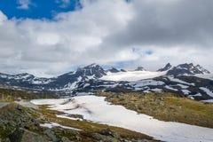 Strada nelle montagne rocciose nevose, Norvegia Fotografia Stock