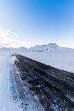 Strada nera attraverso neve Fotografia Stock Libera da Diritti