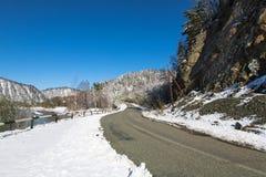 Strada nevosa di inverno sui precedenti delle montagne e del cielo blu Immagini Stock