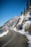 Strada nevosa di inverno sui precedenti delle montagne e del cielo blu Fotografia Stock