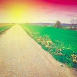 Strada non asfaltata al tramonto Fotografie Stock